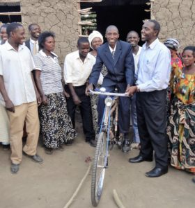 2014-2 Pr. Charles gets on his donated bicyle